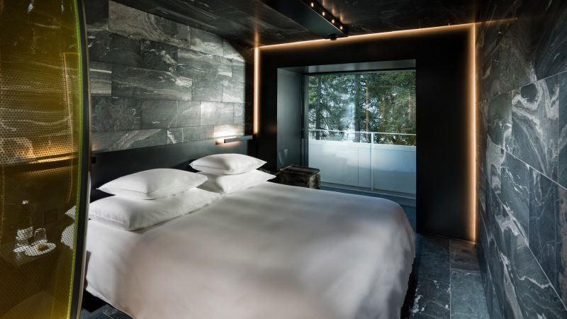 Hotel 7132's wood and stone guest suites feature tinted glass shower