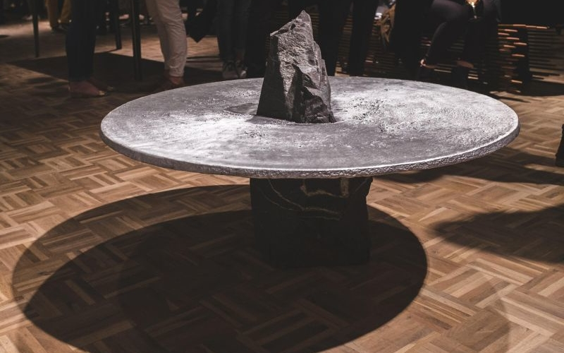 Lunar table by Jesse Ede features monotholic rock pierced through tabletop
