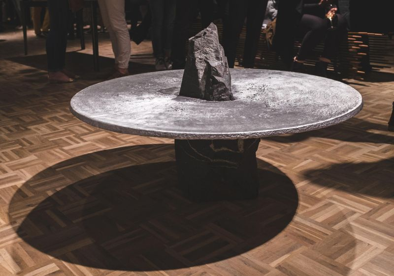 Lunar table by Jesse Ede features monotholic rock piercing through aluminum tabletop