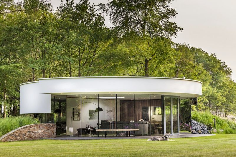 this circular house with big windows brings the outdoors