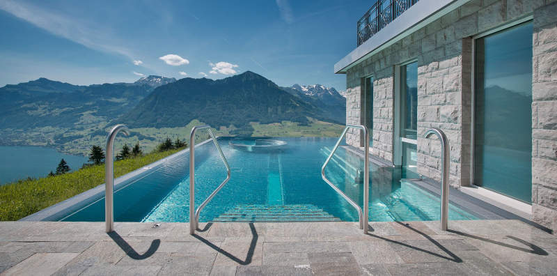 Heated infinity pool at Hotel Villa Honegg offers sweeping views of Swiss Alps