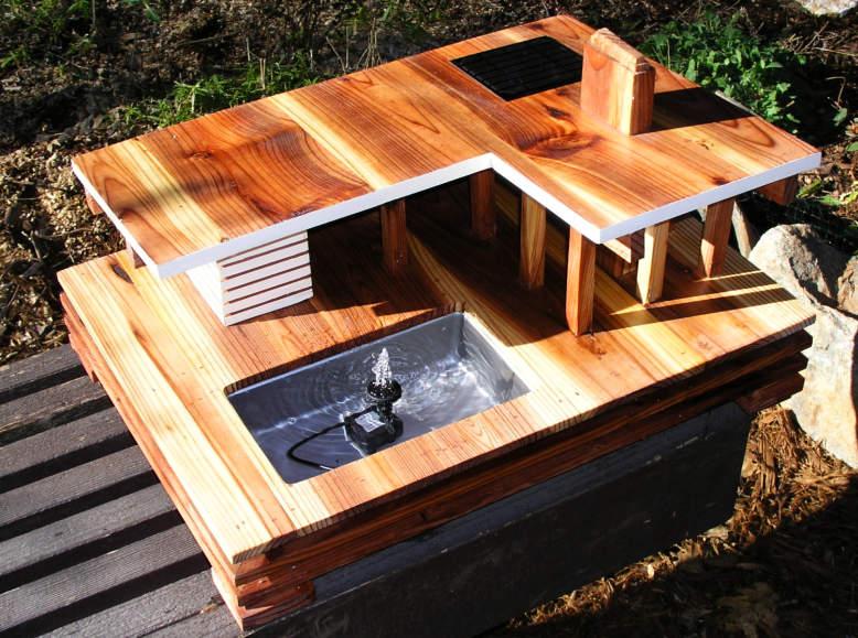 This mid-century modern birdhouse features a solar-powered bird bath