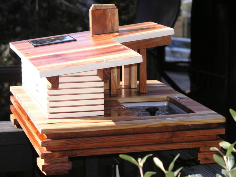 This mid-century modern birdhouse features a solar-powered bird bath