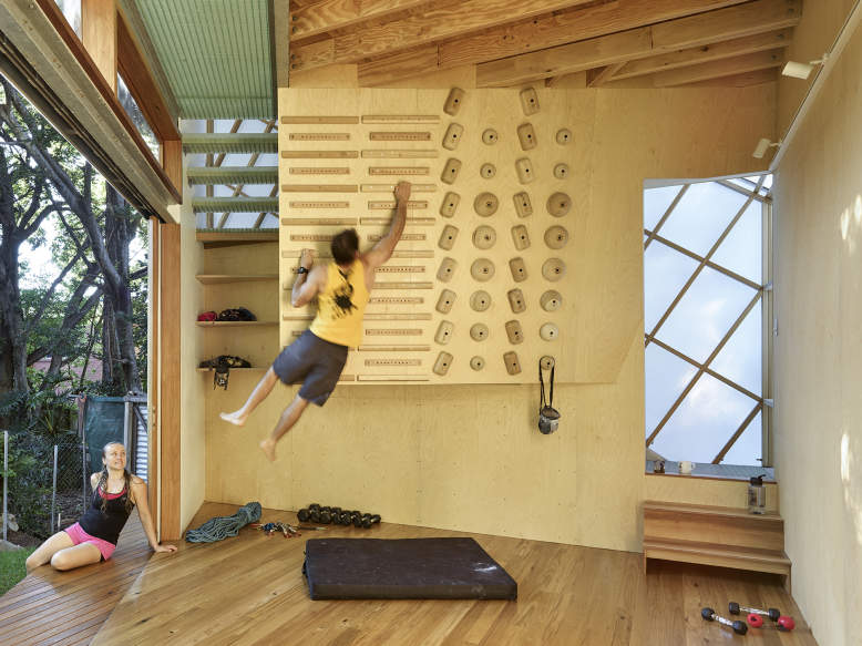 Treehouse-inspired backyard extension with an indoor climbing wall