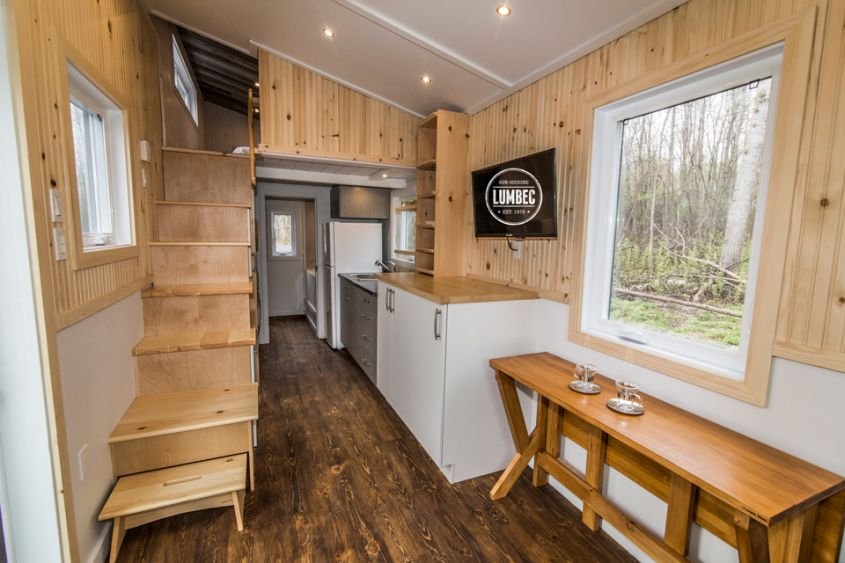 TH2 tiny house on wheels by Lumbec Covered with white pine, stained western red cedar and steel cladding, this 24-foot long tiny house on wheels promises a long life. It has a small living room area with a custom couch and table, a mid-size kitchen, bathroom with tub and a private bedroom loft. Furthermore, storage spaces are scattered throughout the home.