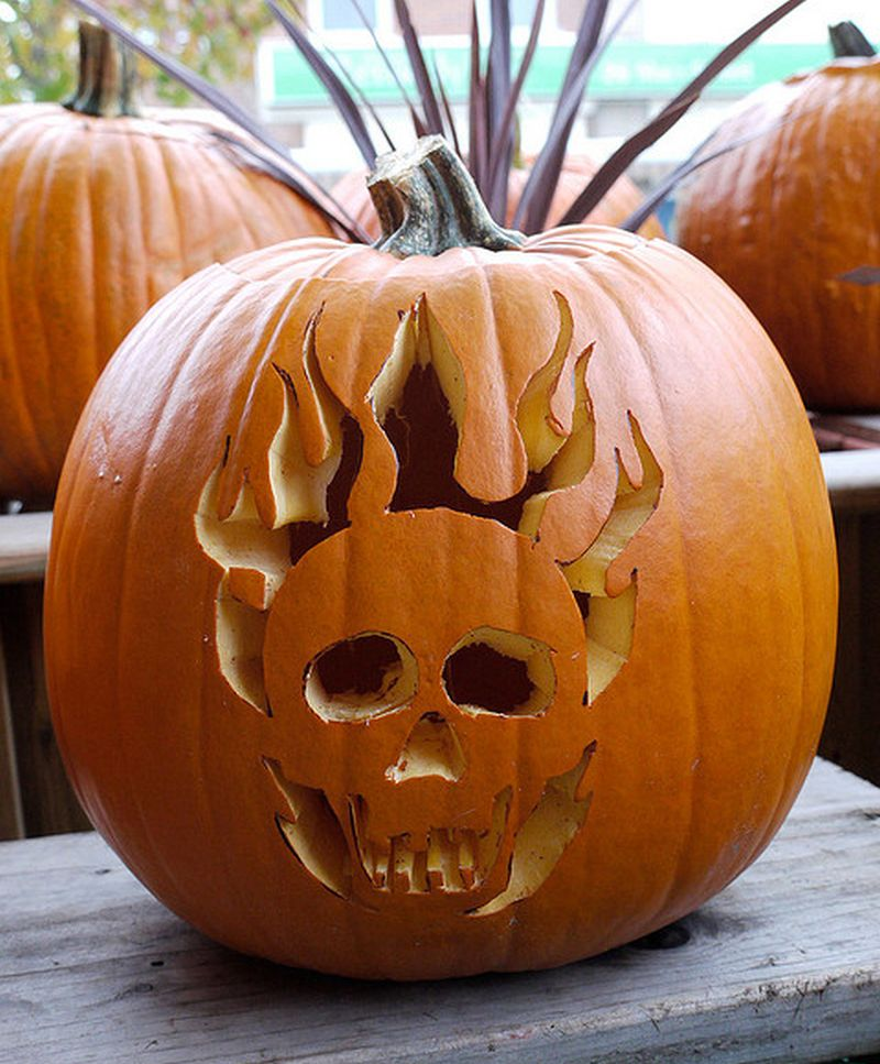 Skull and skeleton-inspired carved pumpkin