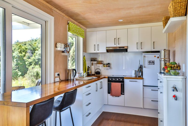 This Off-Grid Shipping Container Tiny Home in New Zealand Charges Electric Car